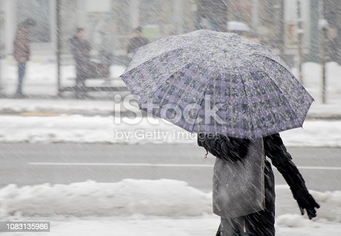 One women walking under umbrella in heavy snowfall in city street