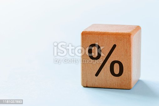 One wooden dice with percent symbol printed on its one side, viewed in close-up with shadow on white background and with copy space