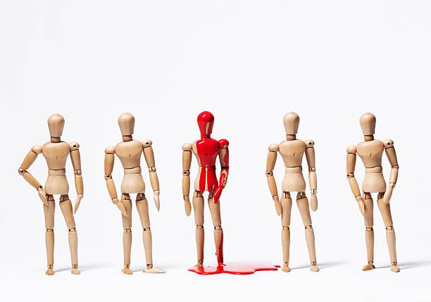 eine hölzerne figur in farbe mit anderen - holzfiguren stock-fotos und bilder