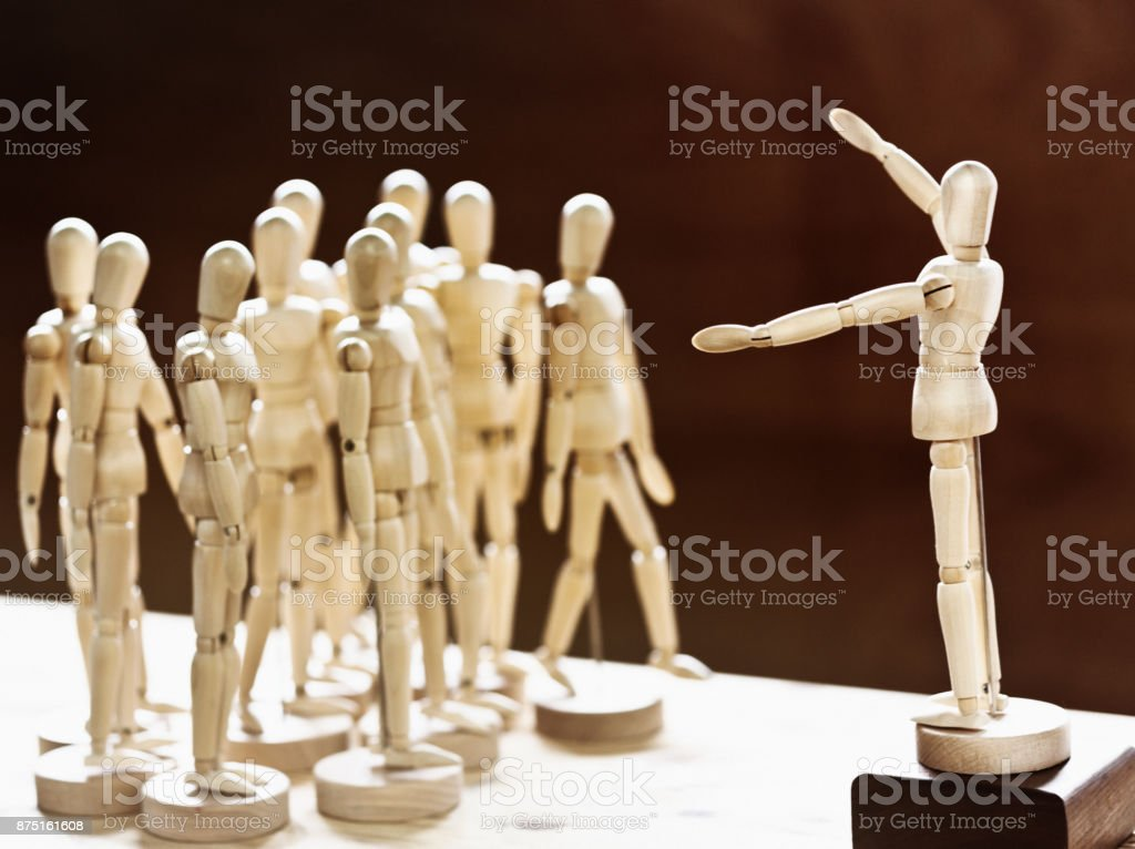 One wooden puppet addressing crowd of others stock photo