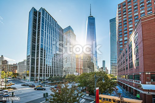 Low angle view of One World Trade Center against sky. Sunlight is streaming through modern office buildings in city. Travel locations.