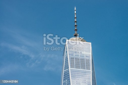 The top section of One World Trade Center in Lower Manhatten, on a clear and sunny day in New York City.