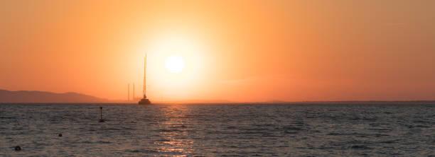 One yacht at the horizon at sunset stock photo