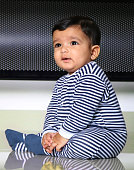 one year old baby boy sitting and smiling with black and white stripe dress