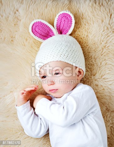 istock one year old baby lying in bunny hat on lamb 517852170