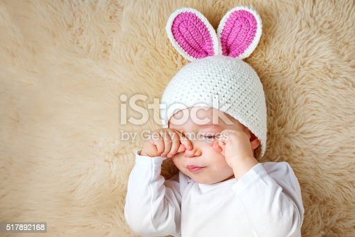 istock one year old baby lying in bunny hat on lamb 517892168
