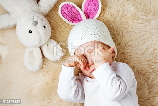 istock one year old baby lying in bunny hat on lamb 517898132