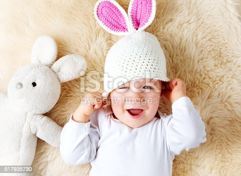 istock one year old baby lying in bunny hat on lamb 517935730