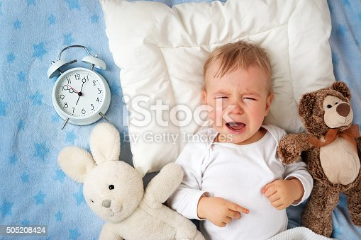 istock One year old baby with alarm clock 505208424