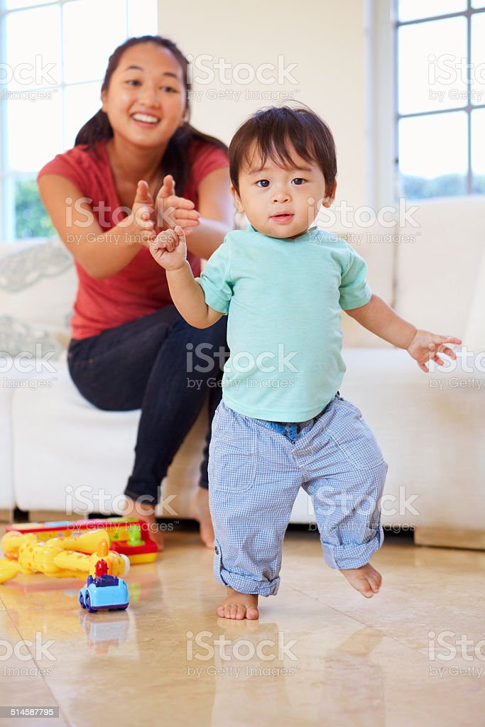 One Year Old Boy Taking First Steps With Mother stock photo