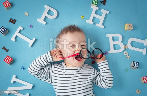 istock One year old child lying with spectacles and letters 936409248