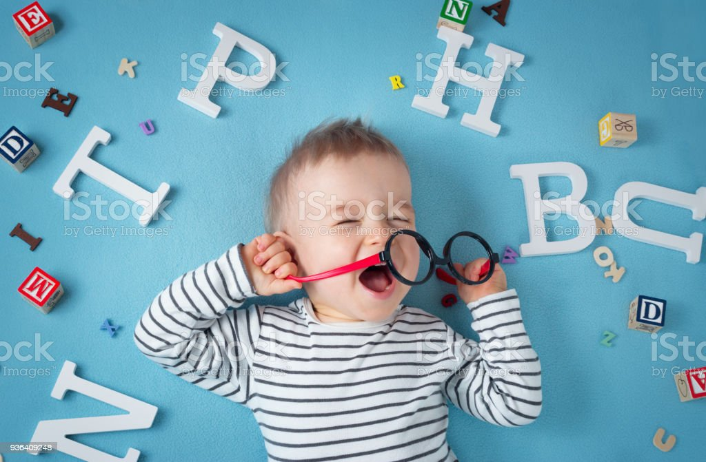 One year old child lying with spectacles and letters stock photo