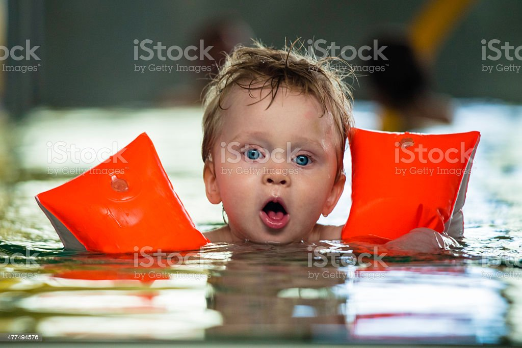 One year old child swims by himself with water wings stock photo