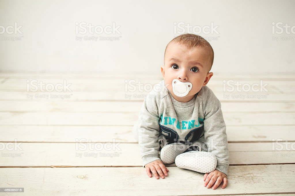 One year old cute baby boy sitting on wooden floor stock photo