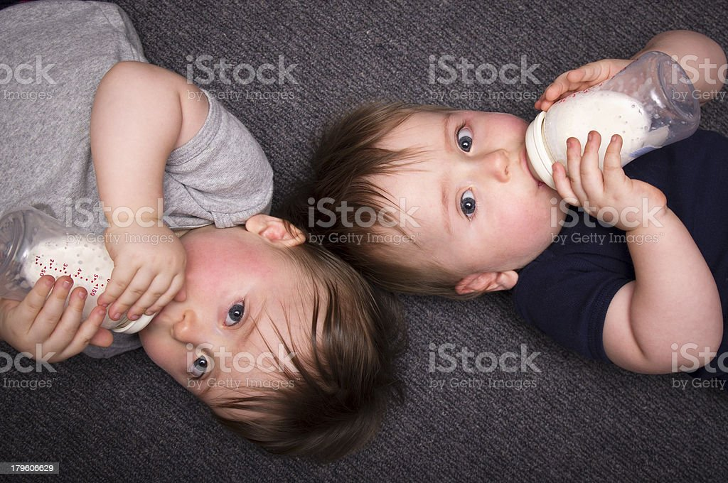 One year old twins drink from a bottle A stock photo of one year old twin boys lying on the ground drinking from bottles. 12-17 Months Stock Photo