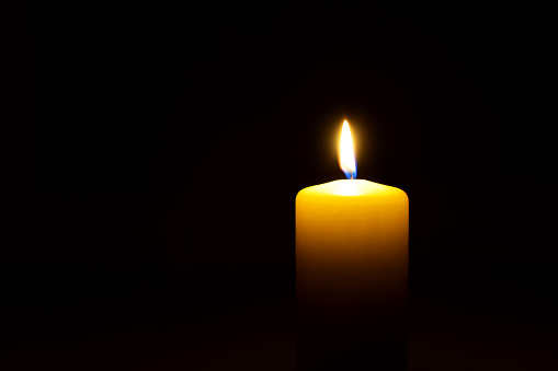 One yellow candle flame  burning in darkness on black background with copy space for text.