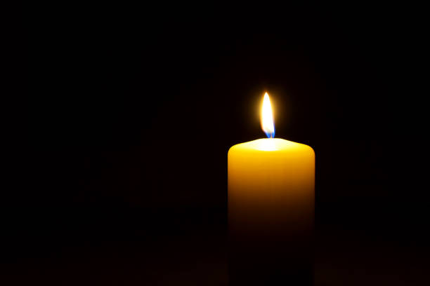 one yellow candle flame  burning in darkness - candle stock pictures, royalty-free photos & images