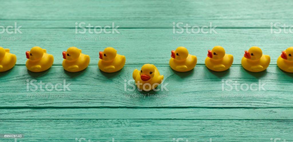 Un canard en caoutchouc jaune, rompant avec une ligne de caoutchouc jaune ordonnée canards se déplaçant dans une direction droite sur un fond de table en bois couleur turquoise. - Photo