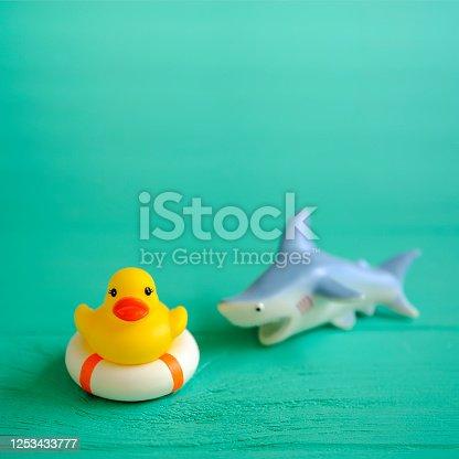 A yellow rubber duck on a safety inflatable life ring trying to escape a ferocious rubber shark nearby, set on a wooden turquoise-colored table background, conceptually representing water. Concept image relating to safety, survival, danger, conquering adversity, escape, danger, hostile environment, etc.
