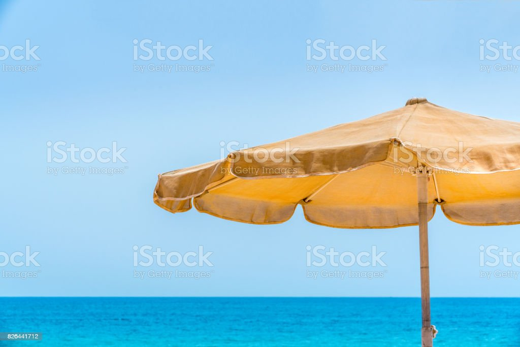 One yellow sun parasol against blue water and sky. royalty-free stock photo