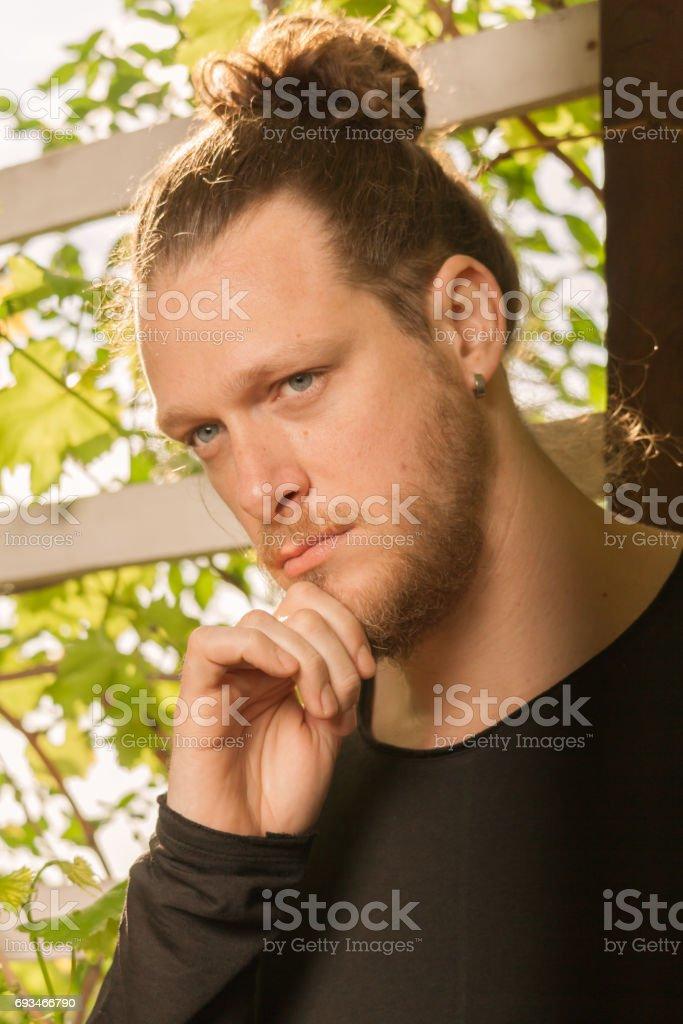 one young adult man, looking sideways, head face portrait, outdoors sunny day, beard, long hair man bun stock photo
