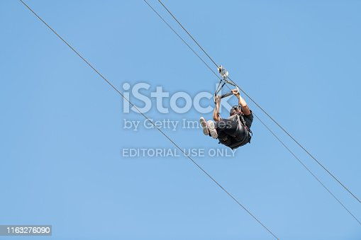 istock One young African american woman against blue sky on zipline or zip line in attraction park in Florida Panhandle 1163276090