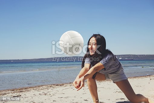 istock One young beautiful lady is playing volleyball on the beach 947970726