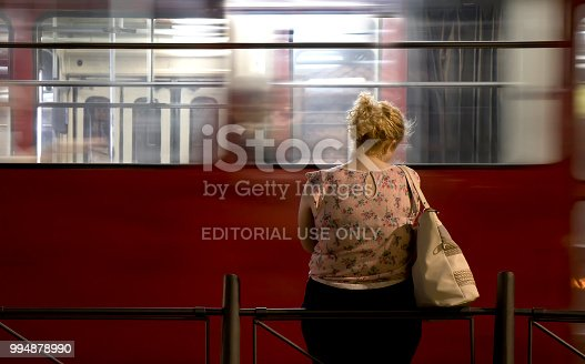 Belgrade: One young blond woman standing alone at a bus stop and waiting for public transportation in the night and an empty tram moving past behind  her