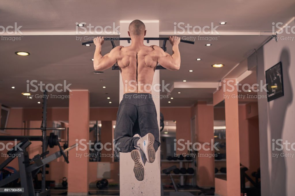one young bodybuilder, rear view, exercise pull-up bar, gym indoors. full lenght shoot. stock photo