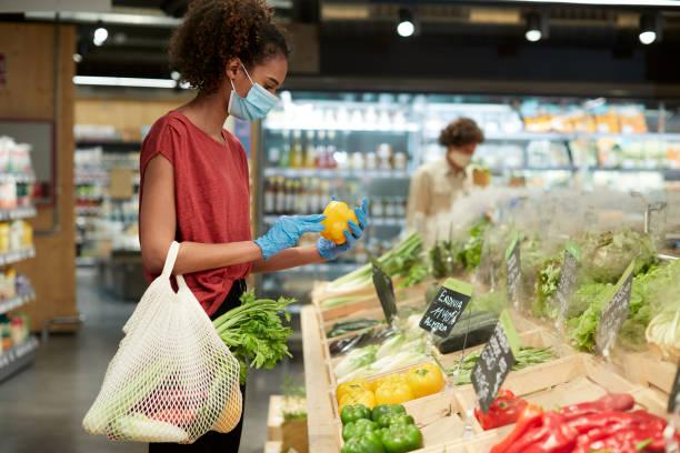 um jovem cliente escolhendo vegetais em um supermercado. - costumer - fotografias e filmes do acervo