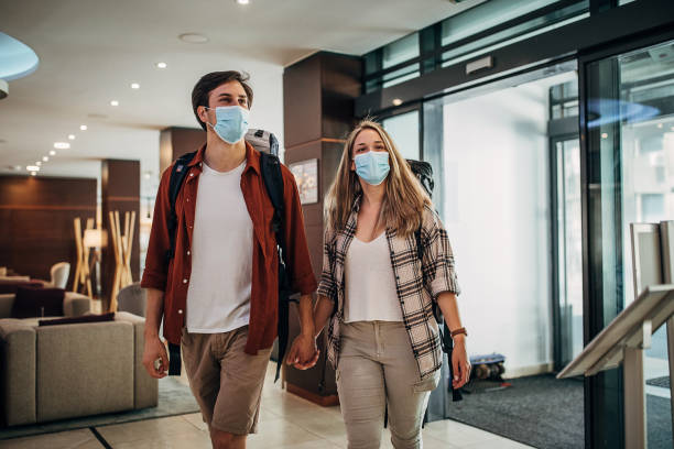 One young couple with protective face masks entering the hotel lobby stock photo