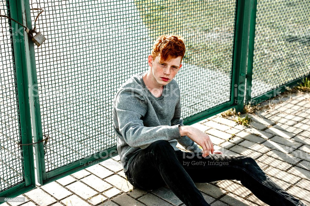 One young handsome red haired fashionable boy sitting near stadium in sunny day outdoor , wearing casual clothing. Close up, retouched shot. stock photo