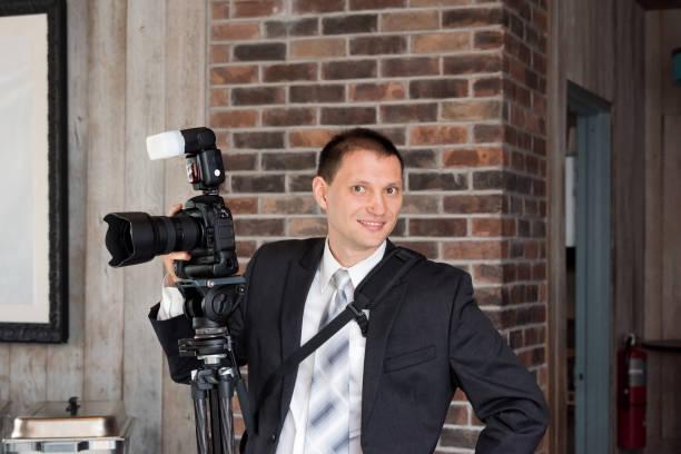 eine junge glücklich lächelnde hochzeitsfotograf in anzug und krawatte stehend mit kamera, externer blitz, stativ im innenraum restaurantgebäude - wedding photography and videography stock-fotos und bilder