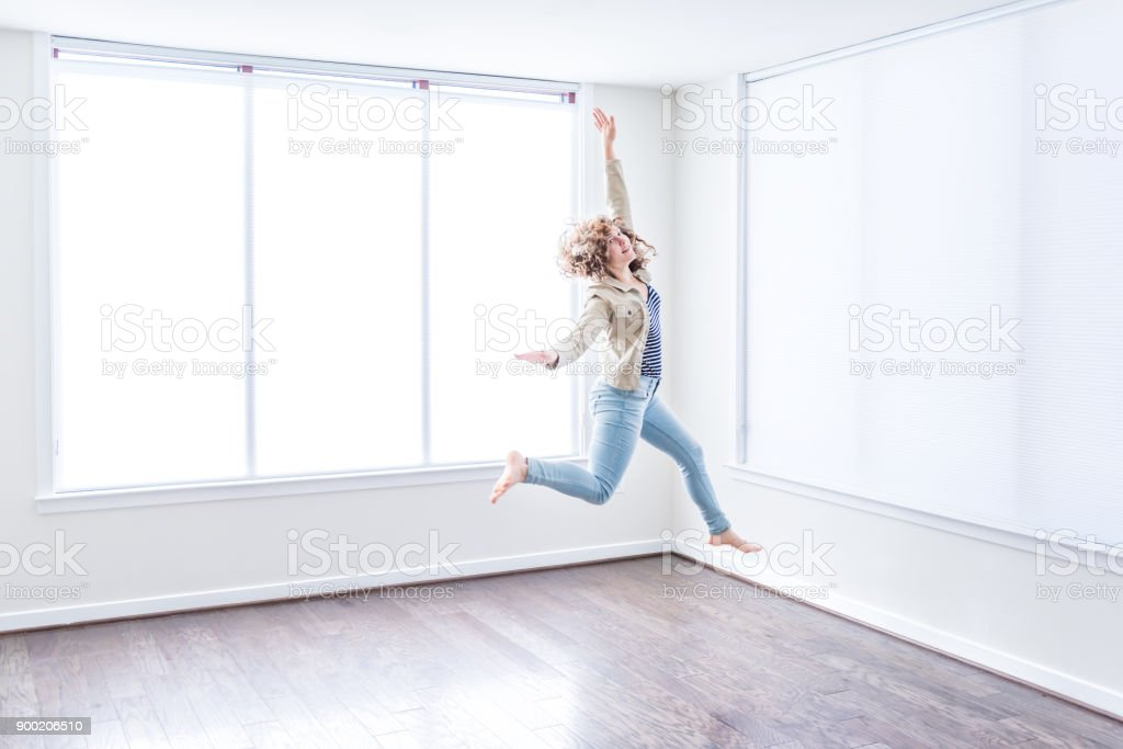 One Young Happy Woman Jumping Up In Empty Modern New Room