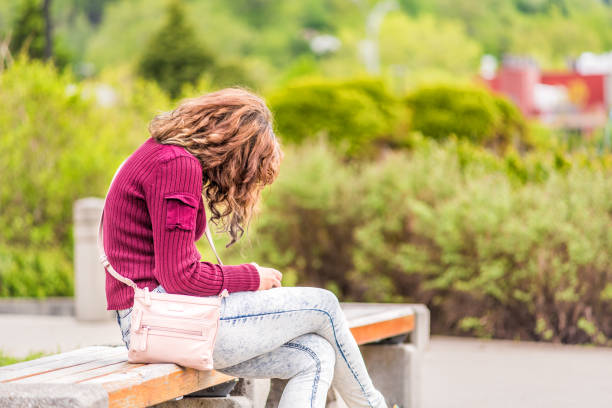 One young happy woman sitting on bench on sidewalk in green downtown city park in Saguenay, Canada, Quebec during summer looking at phone or reading book stock photo