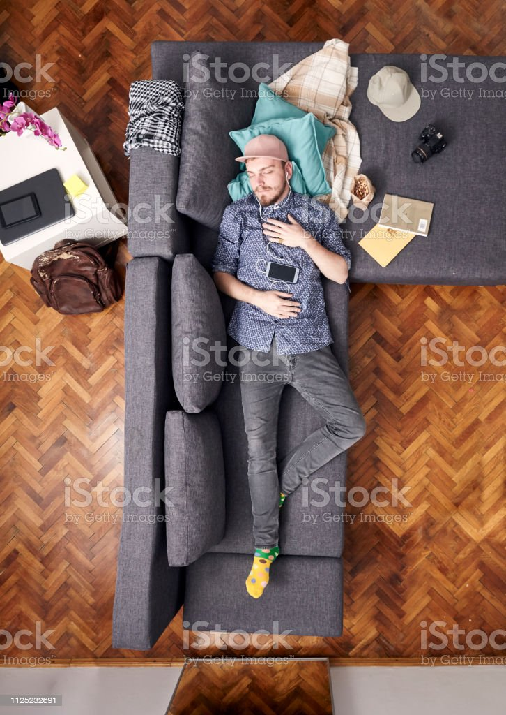 one young hipster man, laying in bed sleeping. whole sofa and bed visible, view from above. stock photo