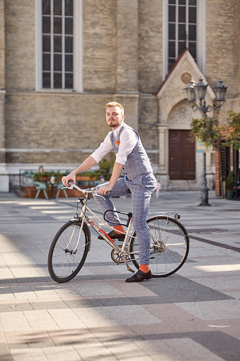 one young man, 20-29 years old, wearing hipster suit, smart casual,  posing on old city bike, outdoors on old European city square (out of focus).