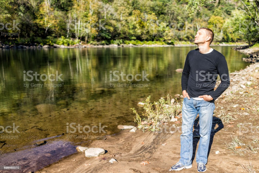 One young man enjoying nature by peaceful, calm river lake during sunny autumn day with reflection stock photo