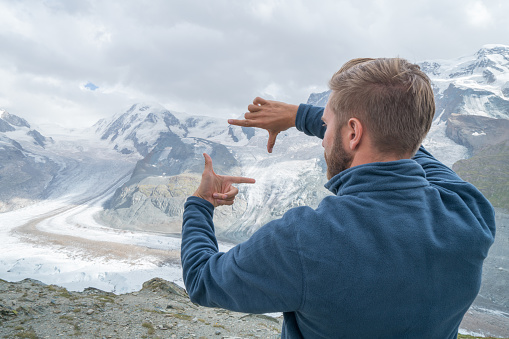 One young man standing in front of a glacier framing the spectacular view with hand frame . People love travel concept.