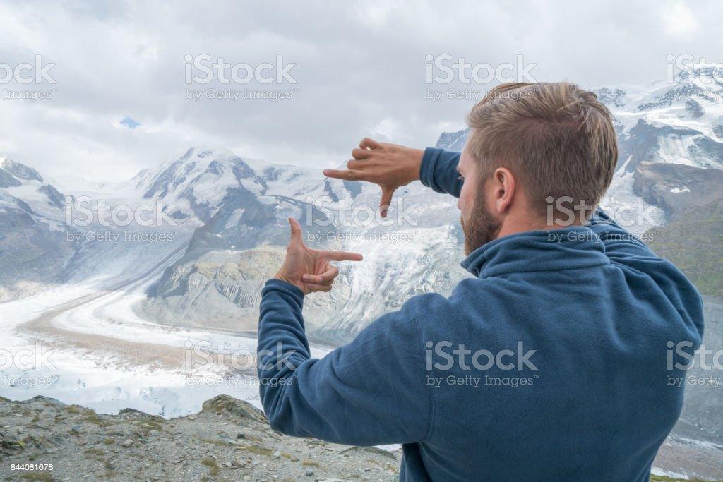 Ein junger Mann Rahmung Gletscher mit Händen, Schweiz – Foto
