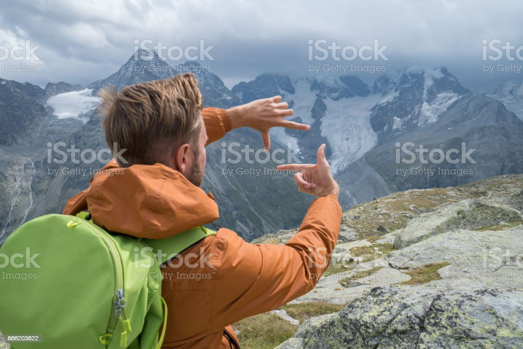 One young man framing mountains, Switzerland stock photo