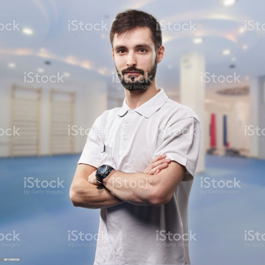 one young man, looking at camera, physiotherapist portrait. in blurred background exercising room. stock photo