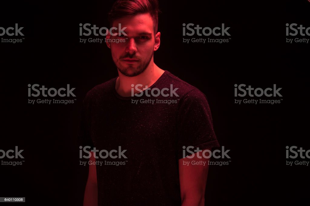 one young man looking at camera, red color light stock photo
