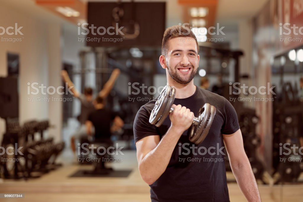 one young man, ordinary average looking, one arm dumbell exercise, smirking, in gym. Unrecognizable group of people behind. stock photo