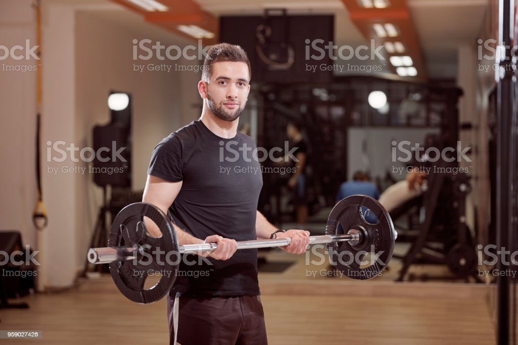 one young man posing, ordinary average looking, holding barbell with weights, exercise in gym. Unrecognizable person behind (out of focus). stock photo