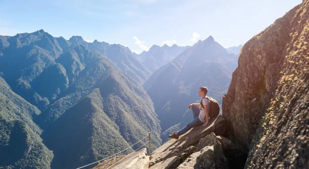Ein junger Mann sitzt auf der Kantenklippe – Foto