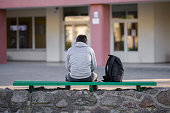 istock One young man sitting on bench at school yard. Break time. Back view. 1227303349