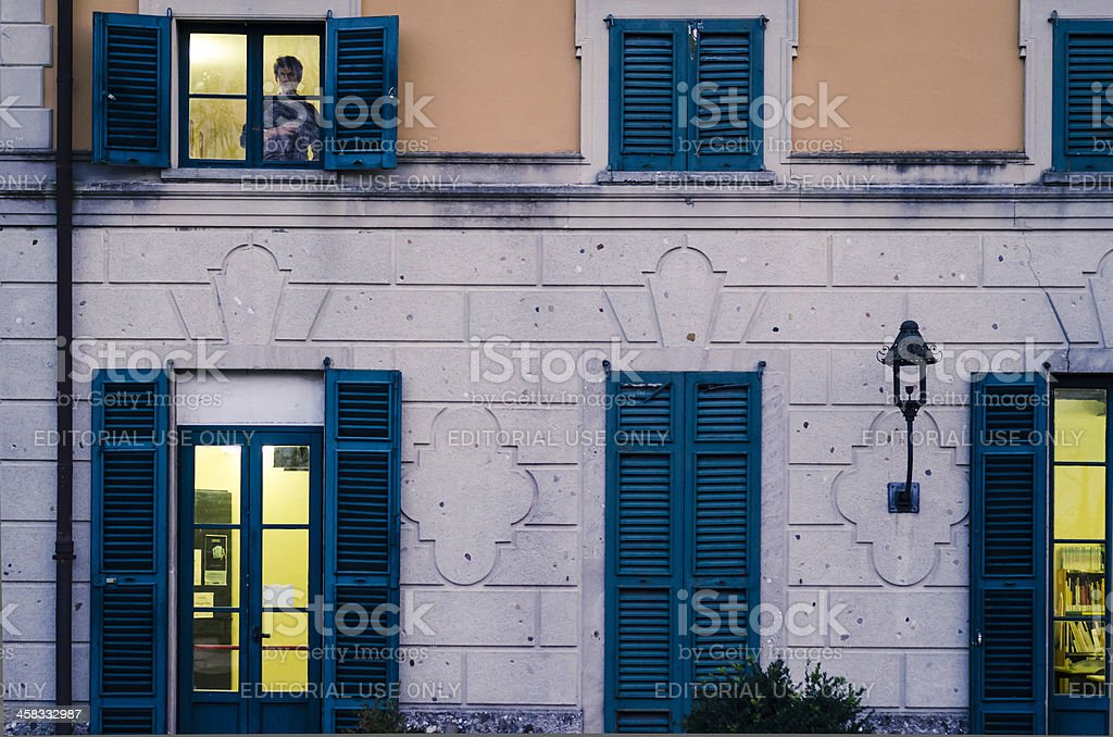 one young man watching out of a window stock photo