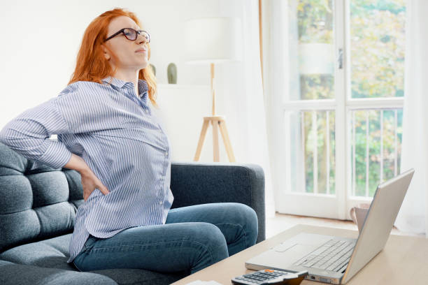 One young redhead woman suffers back pain cramp working at home stock photo