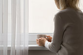 One young sad adult woman sitting at window and holding mug in hands. Looking out from home. Thinking about life. Back view.